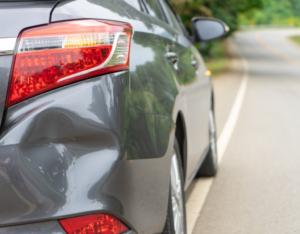 grey car with rear bumper dent