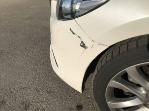 white car that needs paintless dent repair on car scratch